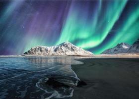 aurora boreal, aurora boreal acima na montanha nevada na praia skagsanden nas ilhas lofoten foto