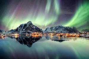 aurora boreal dançando na montanha em uma vila de pescadores foto