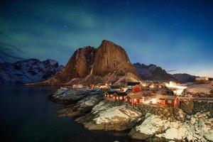 aurora boreal sobre a montanha na vila de pescadores em Hamnoy foto