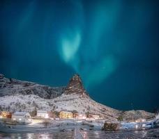 aurora boreal na montanha de neve com vila de pescadores nas ilhas lofoten foto