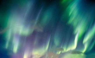 aurora boreal, luzes do norte rodopiam com estrelas no céu noturno foto