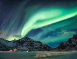 aurora boreal ou aurora boreal sobre montanha nevada no círculo ártico em flakstad nas ilhas lofoten foto