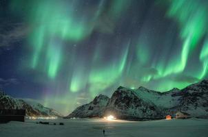 aurora boreal, aurora boreal sobre a montanha de neve e viajante caminhando no inverno nas ilhas Lofoten foto