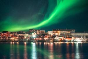 aurora boreal sobre a vila de pescadores na costa de lofoten foto