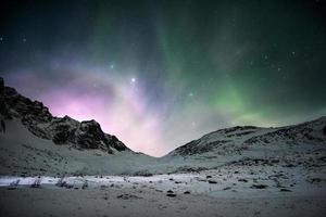 aurora boreal com o nascer do sol brilhando sobre a cordilheira no céu noturno foto