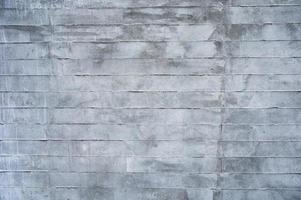 textura de parede de bloco de tijolo de cimento manchado de cinza foto