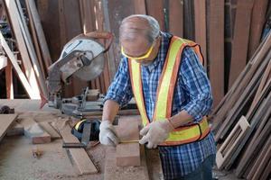 velho carpinteiro asiático trabalhando em uma fábrica de madeira. eles estão usando uma fita métrica e um lápis, além de outros equipamentos industriais, como martelos, serras elétricas e outras ferramentas de artesanato. foto