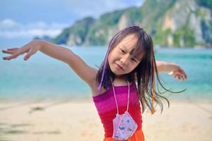 retratos fofos de uma menina asiática sorridente de cabelos negros trançada com fios multicoloridos em um vestido casual arco-íris e máscara facial, bela praia com montanha e mar nas férias de verão. foto