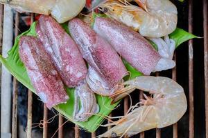 frutos do mar frescos como camarão, lula e peixe são tradicionalmente assados em folhas de bananeira enroladas em uma churrasqueira a carvão. é um jantar delicioso para festas de churrasco, piqueniques ou refeições em restaurantes. foto