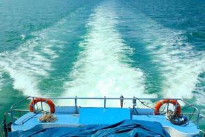 bolhas brancas e respingos de ondas na popa da balsa. feriado viajou no mar. o navio se movia rápido à vista do oceano e ninguém no convés. foto