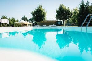 piscina exterior azul no jardim rodeado por árvores foto