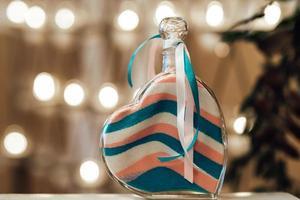 camadas de areia coloridas em um vaso em um coração com foto