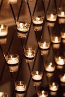 velas queimando em copos no arco do casamento foto