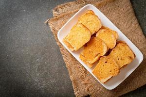 pão crocante assado com manteiga e açúcar no prato foto