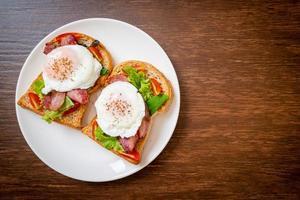 pão integral torrado com vegetais, bacon e ovo ou ovo benedict, no café da manhã foto