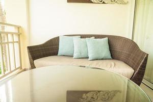 decoração de travesseiro confortável em cadeira de pátio na varanda foto