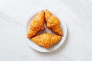 croissant de manteiga fresca no prato foto