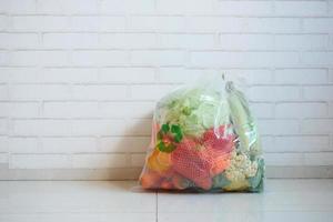 setas recicladas assinam em uma sacola de compras com vegetais no chão foto