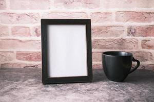 moldura vazia e uma caneca de café no fundo de madeira foto