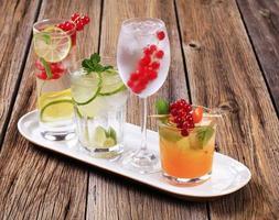 copos de bebidas geladas enfeitadas com frutas frescas foto