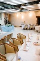 o presidium dos noivos no salão de banquetes do restaurante é decorado com velas e plantas verdes foto