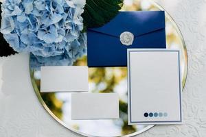 convite de casamento em um envelope cinza sobre uma mesa com ramos verdes foto