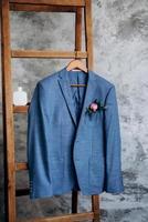 terno clássico blazer azul pendurado em uma escada de madeira foto