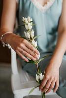 menina noiva em um vestido cinza segurando um galho verde foto