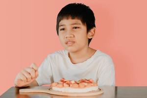 menino bonito asiático sentado à mesa de jantar com pizza na mesa da frente foto