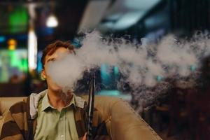 homem no restaurante fumando narguilé foto
