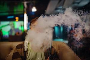 homem no restaurante fumando cachimbo de água. foto