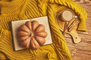 agasalho aconchegante quente, livro aberto e abóbora em fundo de madeira. foto