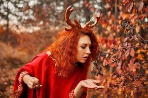 mulher em um vestido longo vermelho com chifres de veado na floresta de outono. foto