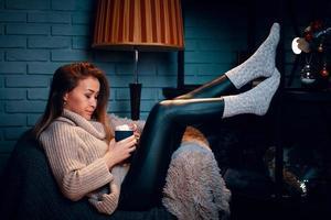 garota séria no suéter na cadeira. foto