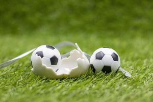 bola de futebol com decoração de feriado de Páscoa em fundo de grama verde foto