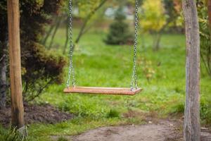 um velho balanço de madeira em um quintal exuberante. foto
