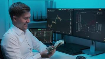 empresário analisando um gráfico de um gráfico da bolsa de valores. jovem empresário do sexo masculino contabiliza o dinheiro ganho com ações da bolsa. diagramas nas telas grandes foto