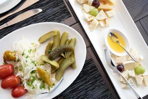 lanches variados. prato de queijo, picles serve no resyaurant. foto