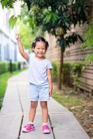 menina feliz parada em uma trilha no parque foto