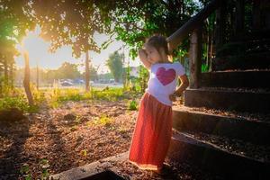 retrato de uma menina asiática feliz em pé no parque com a luz do sol foto