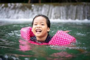 menina asiática usando mangas infláveis nadando na água natural nas férias foto