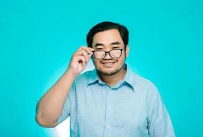 o jovem estava segurando os óculos com um grande sorriso. fundo azul foto