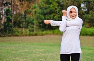 jovem mulher muçulmana fazendo alongamento muscular antes de fazer movimentos de ioga foto