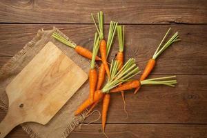 Cenouras frescas em uma tábua de madeira e fundo de madeira foto