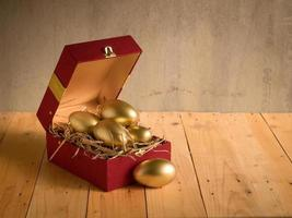 Sucesso financeiro. ovo de ouro em caixa de presente vermelha foto