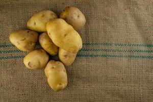 Batatas cruas para cozinhar em esteiras de sacos. foto