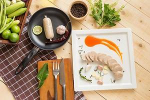 linguiça de porco no vapor em um prato branco servido com molho de pimenta tailandesa tradicional foto
