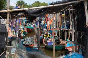 Pequenos barcos de pesca tailandeses atracaram na vila de pescadores durante o dia foto