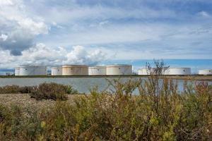 tanques de óleo em uma fileira sob o céu azul, grande tanque industrial branco para gasolina, planta de refinaria de petróleo. energia e poder foto