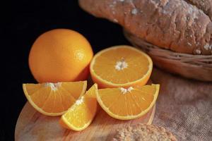 fatias de laranja e laranja na mesa de madeira foto